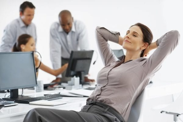 Female executive relaxing with hands behind head in office